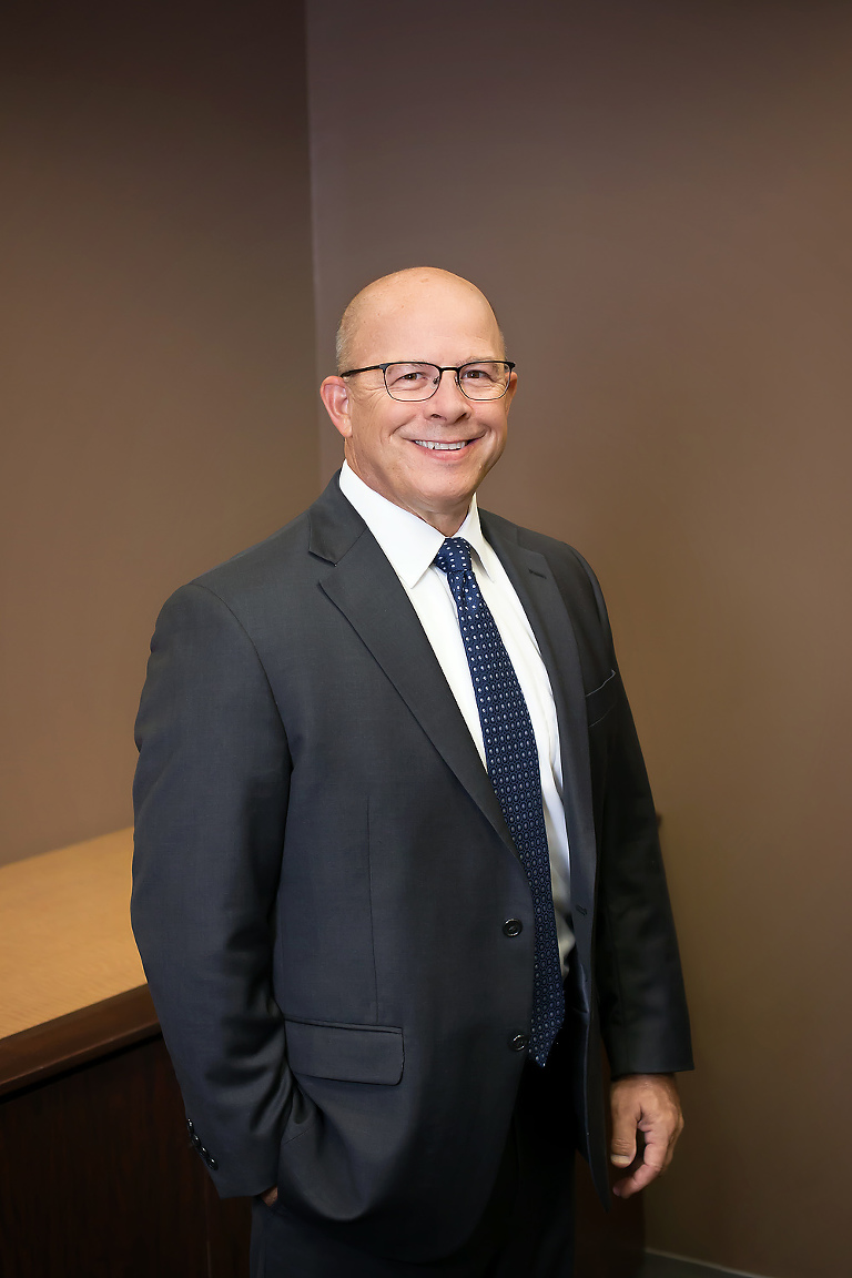 professional headshot of a man standing in his office